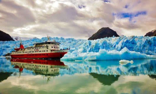 Red cruise ship passes by ice field