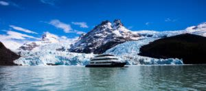 Cruise ship passes by snowy mountain in Chile