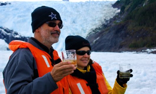 Cruise ship travelers hold drinks near glacier