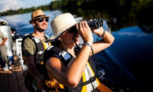 Delfin Cruise travelers use binoculars