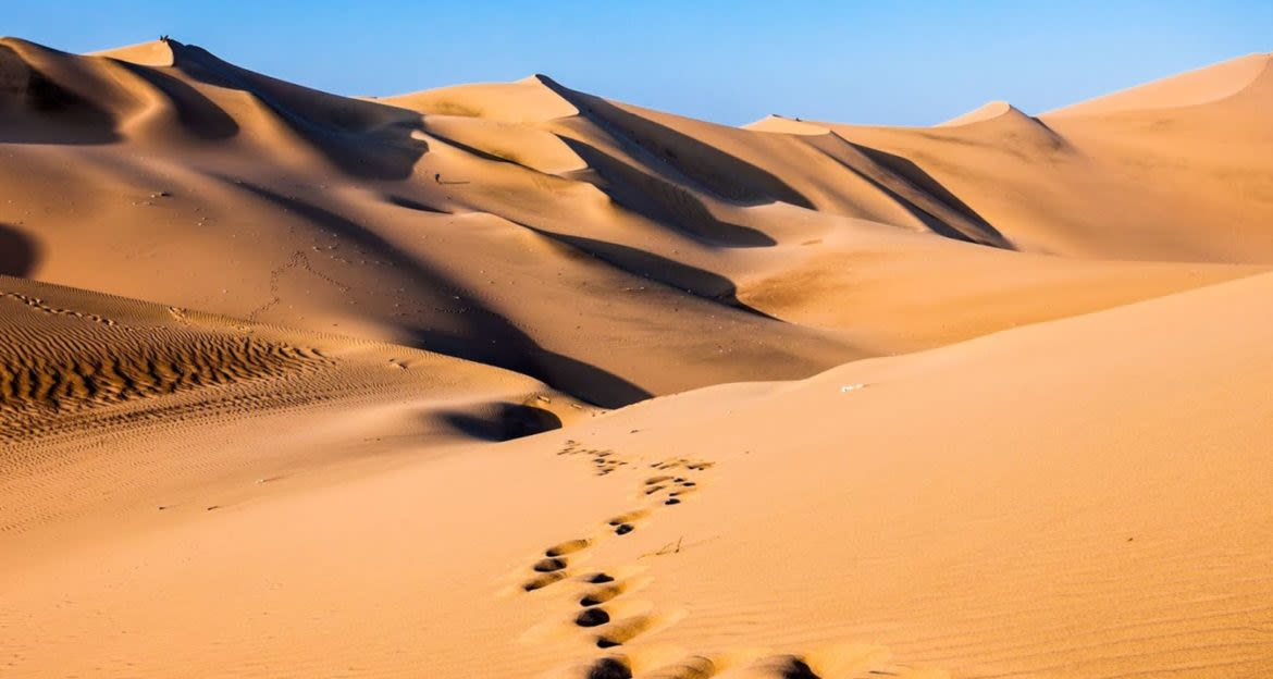 Dunes of desert with footsteps in sand