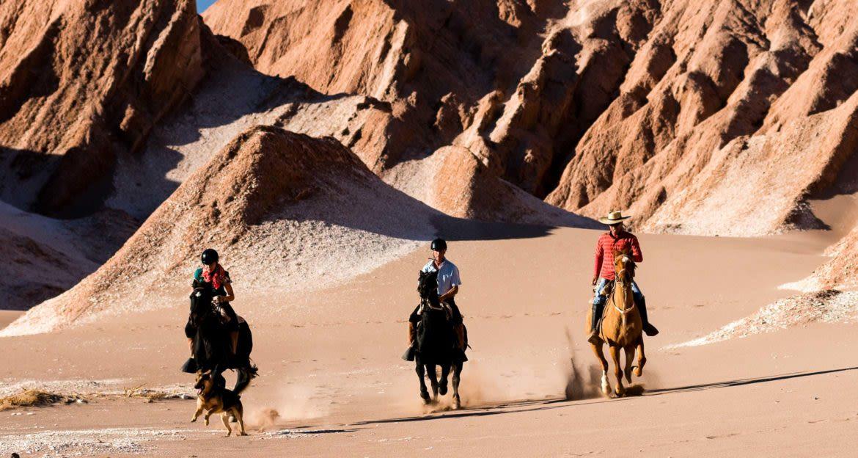Travelers ride horses through desert