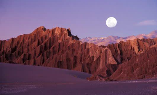 Full moon hangs above desert peaks