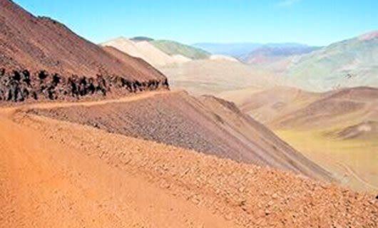 Desert road winds along edge of dune