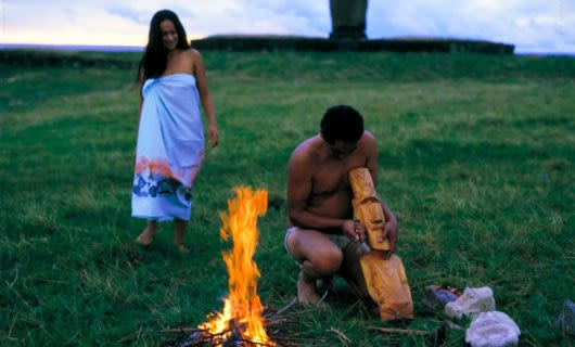 Two people near small fire on Easter Island