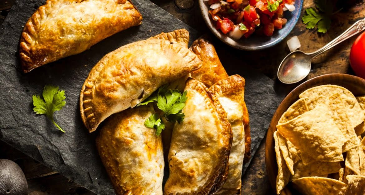 Empanadas laid out on stone platter