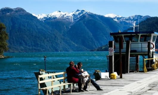 Travelers sit on ferry dock