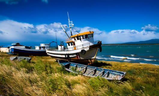 Fishing boat rests on coast near ocean