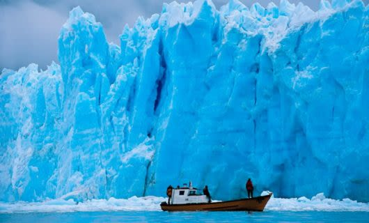 Fishing boat sits near glacier wall