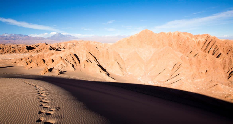Footsteps in sand near desert mountains