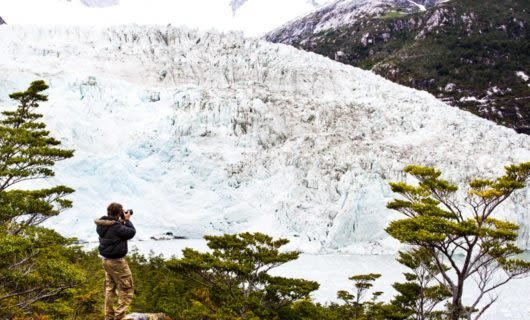 Photographer points camera at large glacier