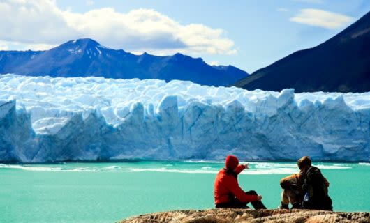 Two travelers sit to look at glacier, one pointing