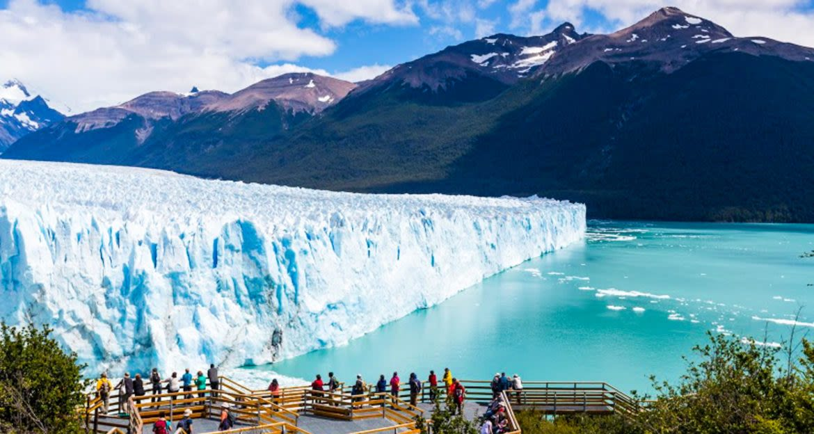 Tourists stand on viewing platform to look at glacier