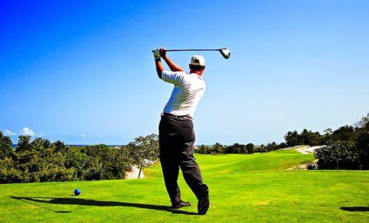 Golfer swings club on sunny golf green