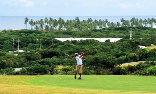 Golfer swings club on coastal golf course