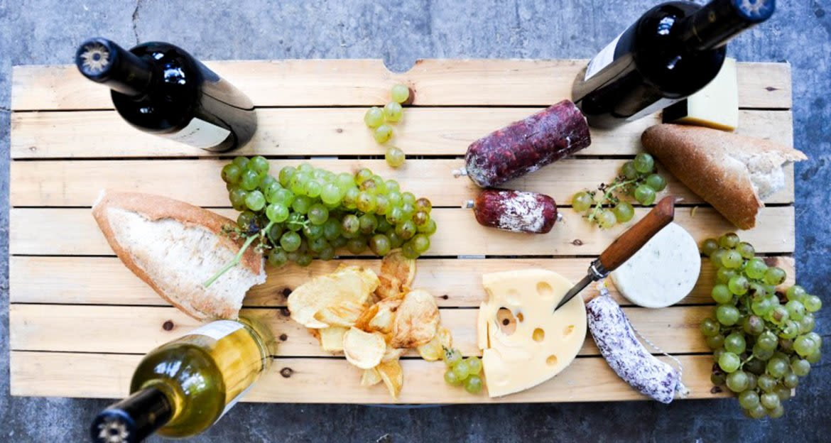 Top-down view of table with wine, grapes, cheese, and bread