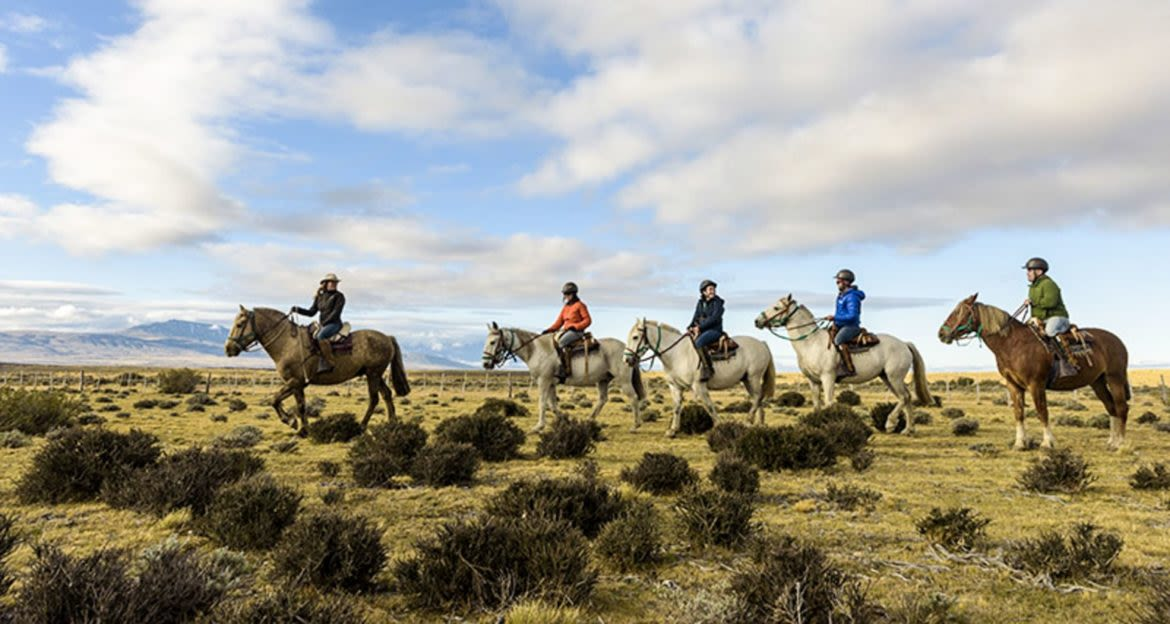 Travelers ride horses in line on plains