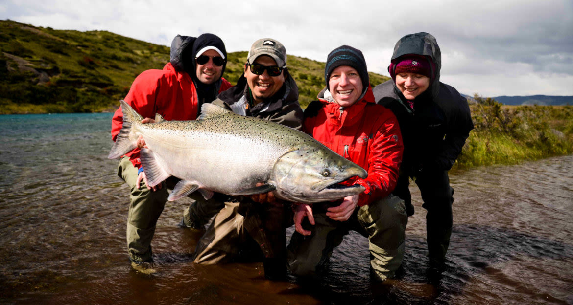 Four people hold large fish