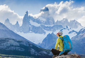Hiker sitting in front of Patagonia mountain peaks