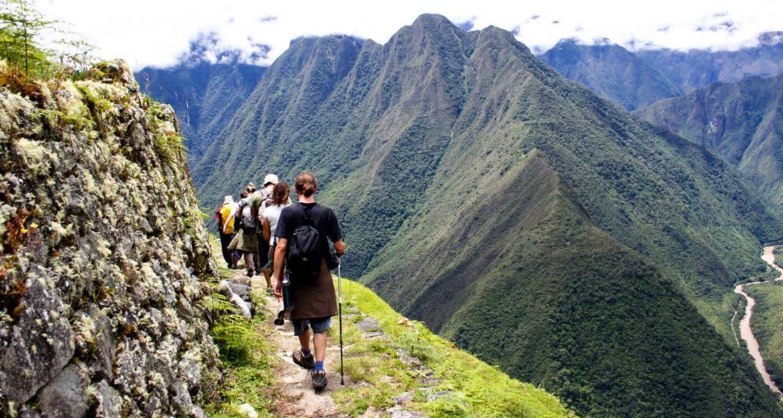 Hikers trek along cliffside trail