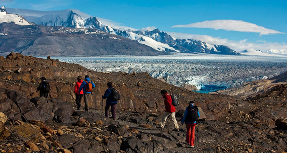 Group of hikers pass large glacier