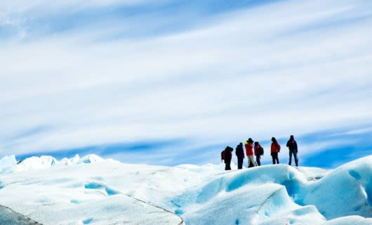 Group of hikers stand on top of glacier