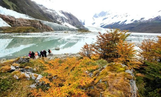 Group of hikers on edge of river in autumn