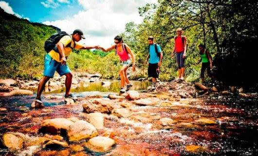 Hikers help each other across rocky stream