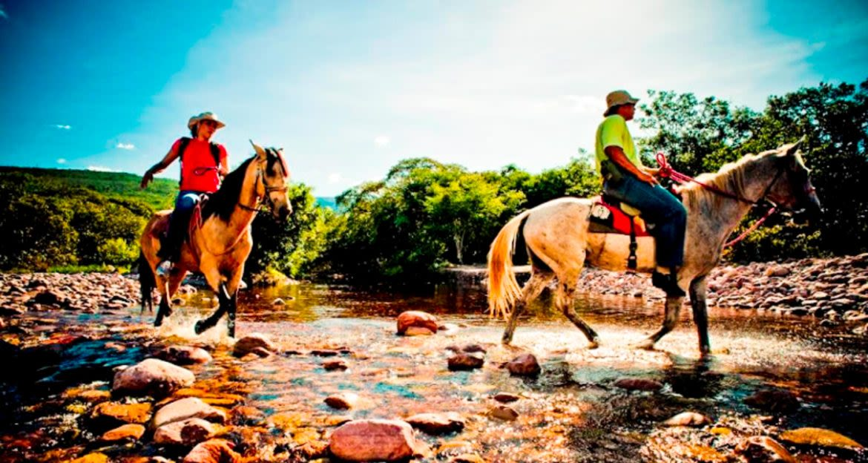 Travelers ride horses down river