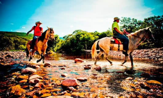 Travelers ride horses down river