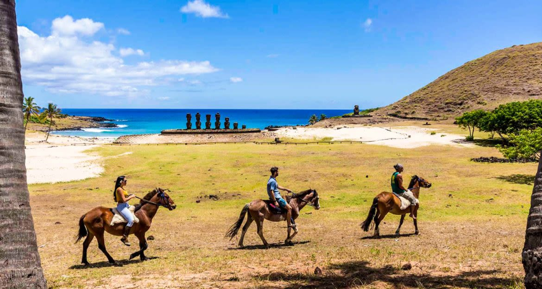 Travelers ride horses along beach near row of stuatues
