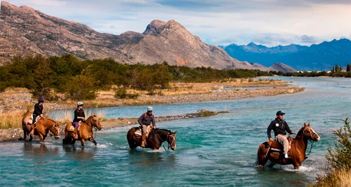 Group of horseback riders cross river