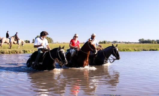 Travelers ride horse through river