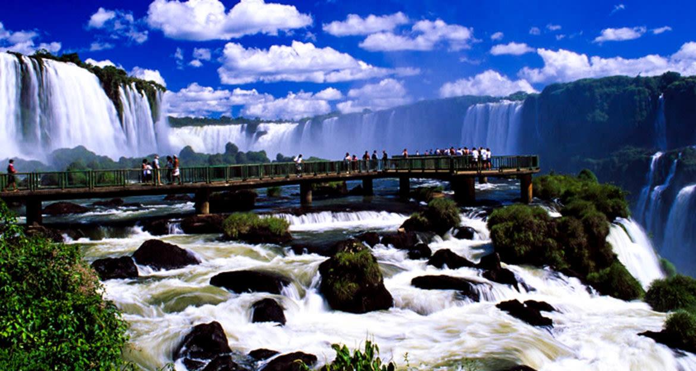 Tourists walk along catwalk above Iguazu Falls