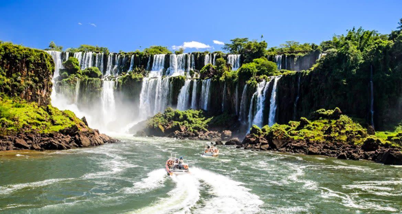 Boats of tour groups approach base of Iguazu Falls