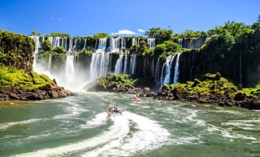 Boats of tour groups approach base of Iguazu Falls