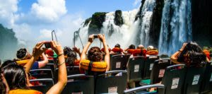 People aboard a boat taking photos of the base of the waterfalls on one of our Iguazu Falls tours