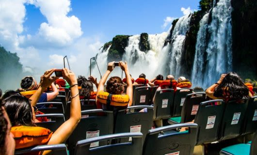 Tourists take photos of Iguazu Falls from boat