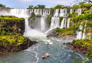 Two boats approach the Iguazu Falls on the Argentine side