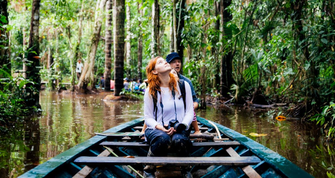 Traveler in canoe looks up at jungle canopy