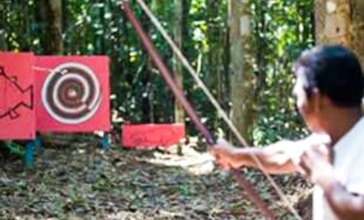Man does archery in the jungle
