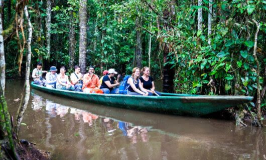 Tour group rides through jungle in long canoe