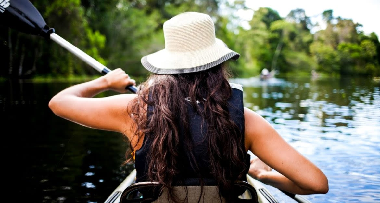 Back view of woman paddling kayak down river