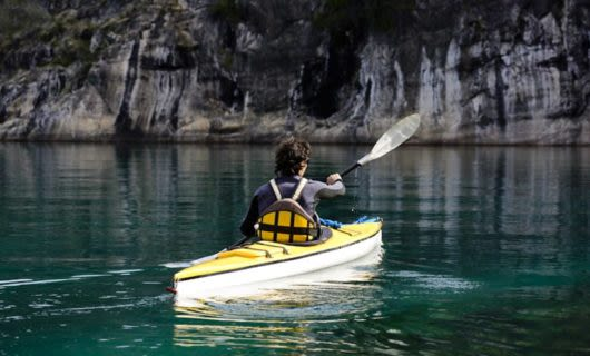 Traveler paddles kayak near cliff