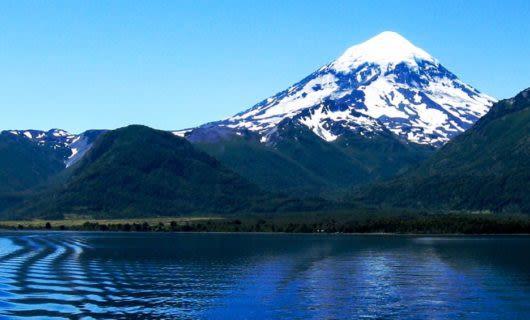 Mountain peak rises over rippling lake
