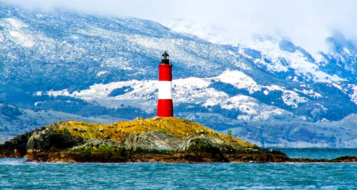 Lighthouse on island near mountains