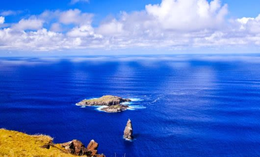 Rocks of Moto Nui Islet in blue ocean