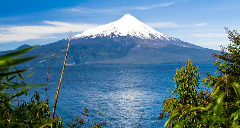 Single mountain peak behind calm lake