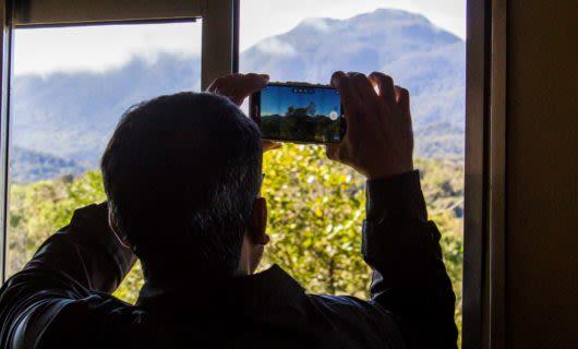 Man takes picture of mountain through phone