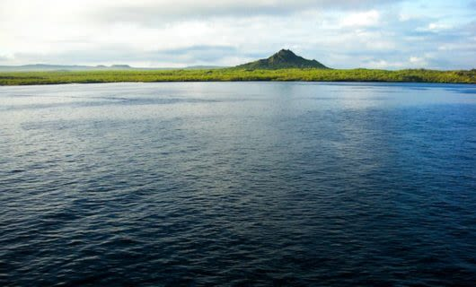 View of distant Galapagos coast and mountain across ocean